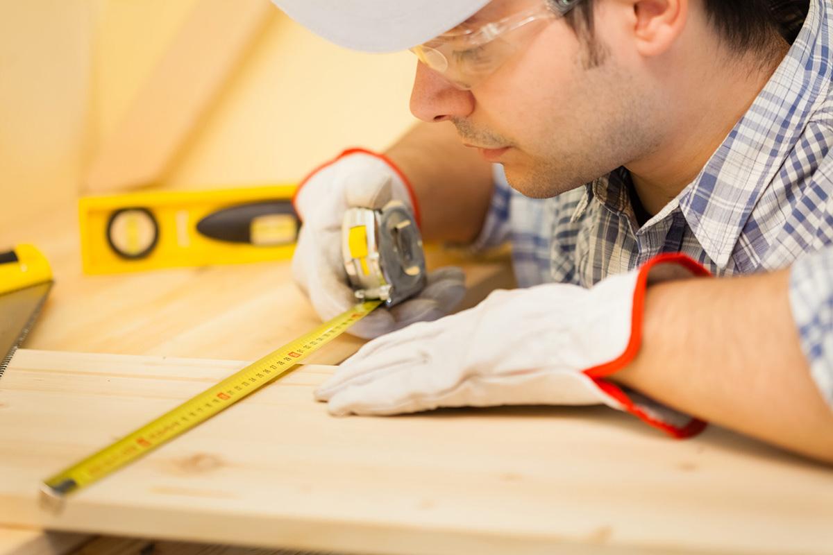 Worker measuring wood board